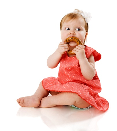 poco: Bebé de un año comer sabroso cookie aislado en blanco Foto de archivo