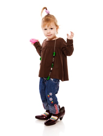 Funny little girl wearing mothers shoes isolated on white photo
