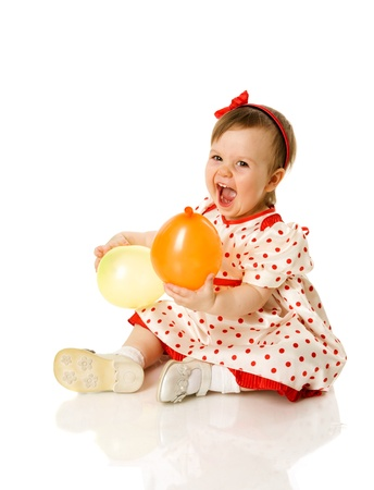 One year girl sitting holding balloons isolated on white photo