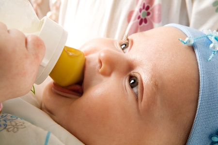 Adorable three month Baby eating from bottle smiling photo