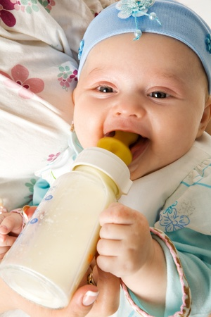 sucking milk: Adorable three month Baby eating from bottle smiling Stock Photo