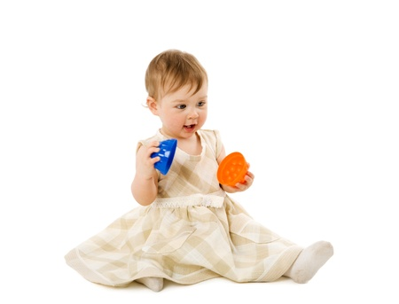 Baby girl playing with toy wearing pink dress isolated photo