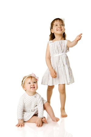 Two little Sisters looking up with interest isolated on white Stock Photo - 8920872