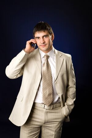 hurrying: Businessman talking on cell phone over dark background
