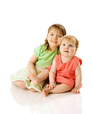 woman sitting floor: Two little Sisters playing together isolated on white Stock Photo