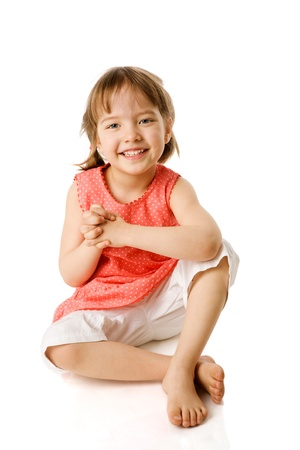Happy Little girl sitting isolated on white photo
