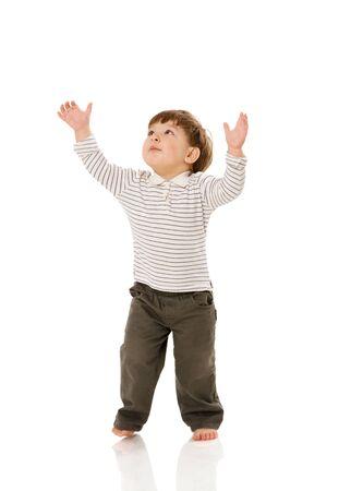 bambini pensierosi: Due anni ragazzo in piedi che punta fino isolated on white Archivio Fotografico