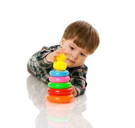 boy playing with colorful pyramid toy isolated on white photo