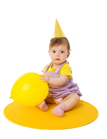 One year baby girl wearing cap holding balloon isolated photo