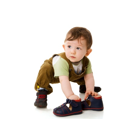 bambini pensierosi: One year Baby boy playing with shoes isolated on white