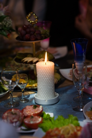 Beautiful burning candle at dinner table special event photo