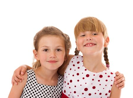 Two happy little sisters portrait isolated on white