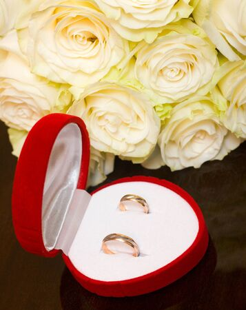 wedding rings in red box near bouquet on table Stock Photo - 10337670