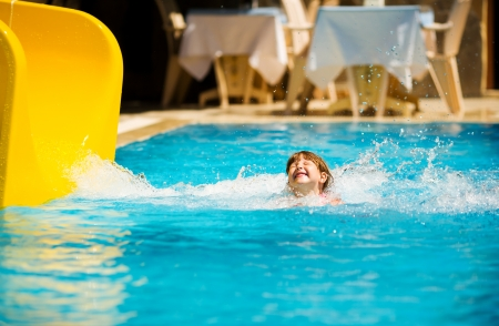 Girl Sliding in pool during Turkey vacations summer holiday photo