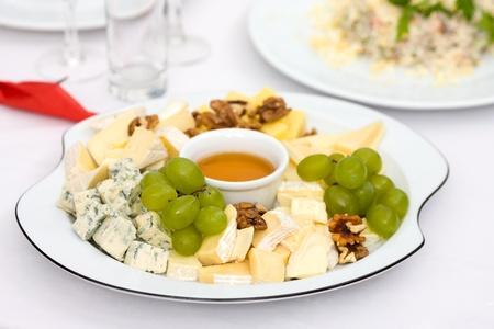 tabla de quesos: Placa de queso con nueces y miel en mesa de restaurante Foto de archivo