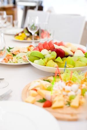 buffet food: manzanas, fresas de sand�a y otras frutas en mesa de caf� Foto de archivo