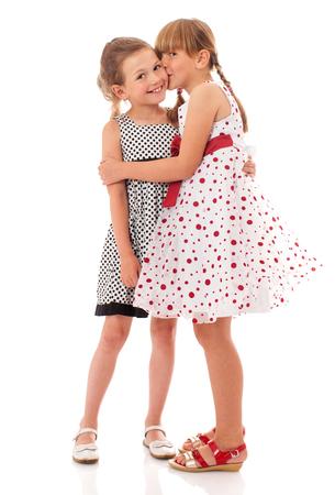 petite fille avec robe: Deux petites s?urs heureux embrassant isolé sur blanc Banque d'images