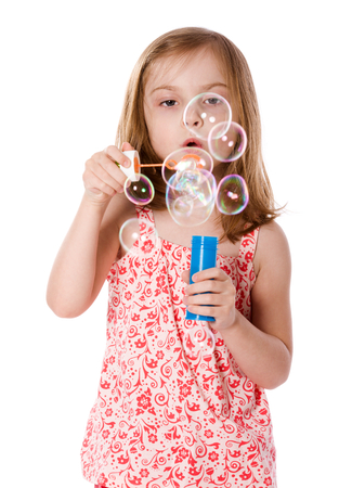 grinning: Happy Girl playing with soap bubbles isolated on white