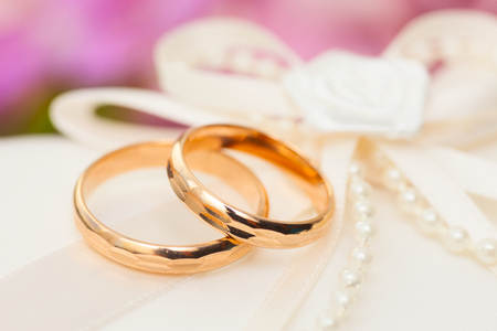 purls: Two Golden Wedding Rings with purls on pillow Stock Photo