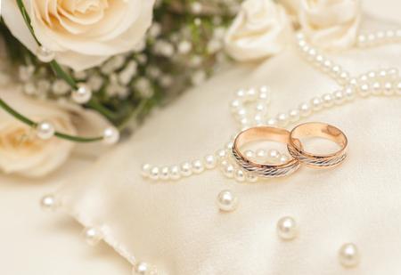 枕の上の purls と 2 つの黄金結婚指輪 写真素材 - 64902805