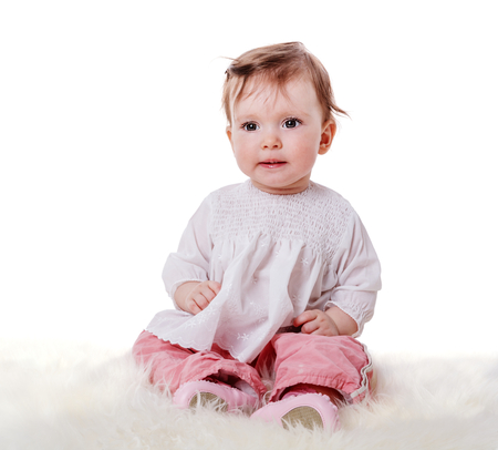 10 month: Curious Baby sitting on fur looking at you isolated on white Stock Photo