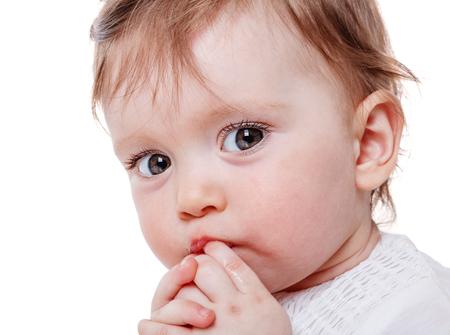 petite fille triste: Close up Portrait de petite fille doigt sucer isolé sur fond blanc