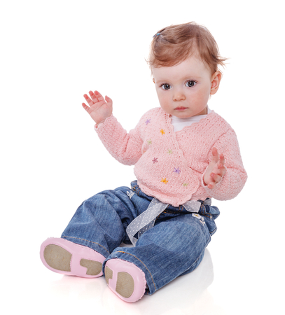 One year baby girl sitting clapping palms isolated on white