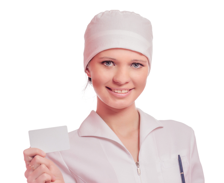 Beautiful young nurse holding business card isolated on white