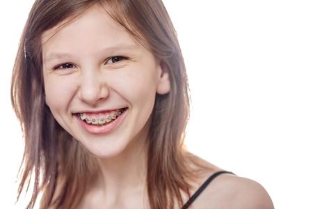 Lachende tiener meisje dragen bretels op zoek naar camera op wit wordt geïsoleerd