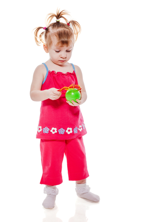 Little girl playing with ball isolated on white
