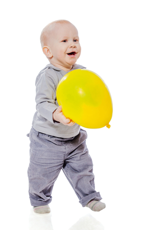 cheer full: Toddler boy playing with balloon isolated on white