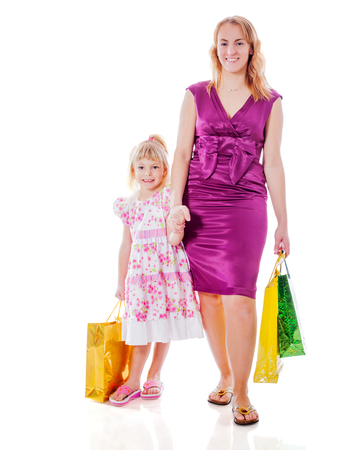 affectionate actions: Mother and daughter walking holding shopping bags isolated Stock Photo