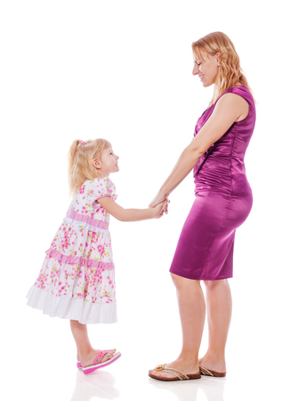 Mother and daughter standing holding hands isolated