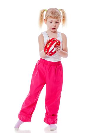 pantalones abajo: Niña jugando con pandereta aislados en blanco Foto de archivo