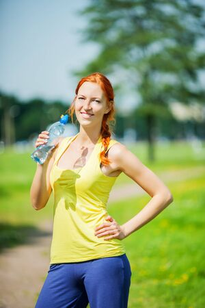 Athlete woman drinking water hot summer day photo