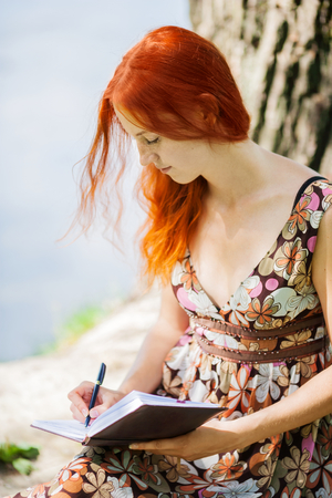 Young redhead woman writing in summer park photo