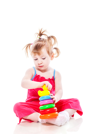 Little girl playing with pyramid isolated on white Stock Photo