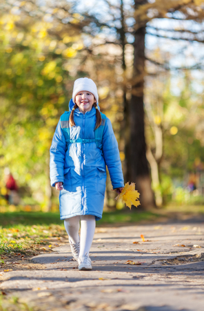 Seven years girl walking holding maple leaves bouquet