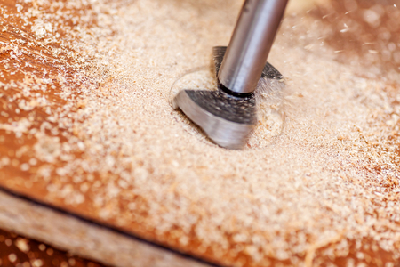 Forstners cutter bit for concealed hinge holes with sawdust Stock Photo
