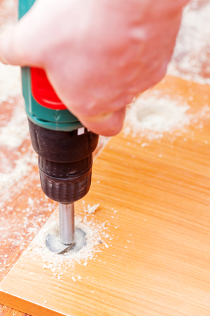 Man drilling holes for concealed hinges process closeup