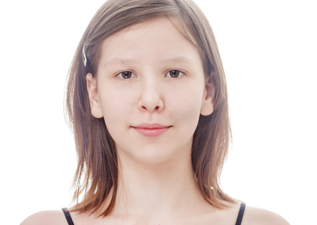 Pensive teen girl smiling and looking at camera isolated on white