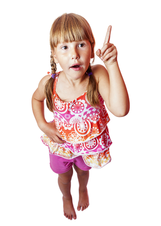 Happy smiling seven years girl pointing up isolated photo