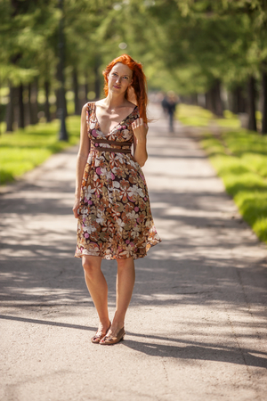 Happy Young redhead Woman smiling in summer park photo