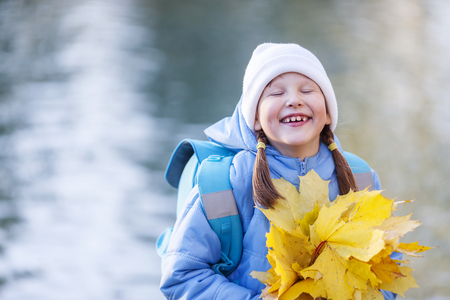 Seven years girl holding maple leaves bouquet