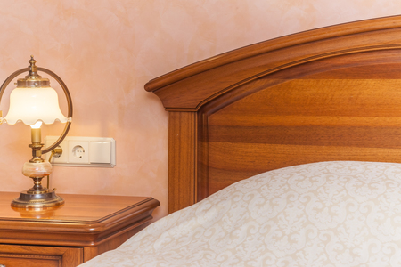 Warm cozy lamp near bed on nightstand