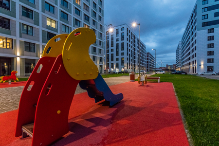 Colorful playground equipment for children in apartment building yard in evening
