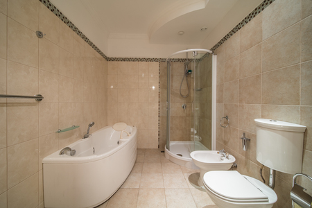 Spacious Beige Tile Bathroom With Bath Tube Sink And Toilet Stock ...