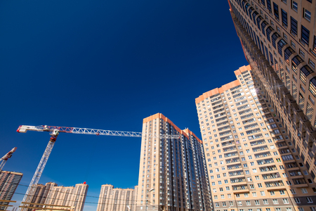 Construction of new real estate apartment buildings over blue sky