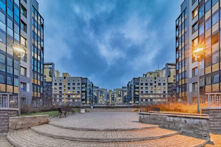 New modern residential buildings with lit windows in evening suburbia district