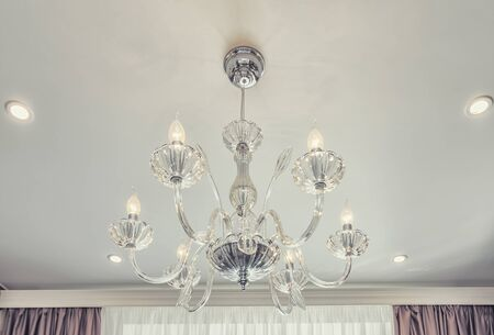 Huge chandelier close up with electric bulbs on fancy ceiling